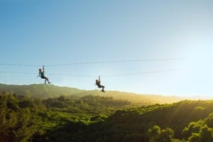 Two people enjoying an Oahu zipline tour.