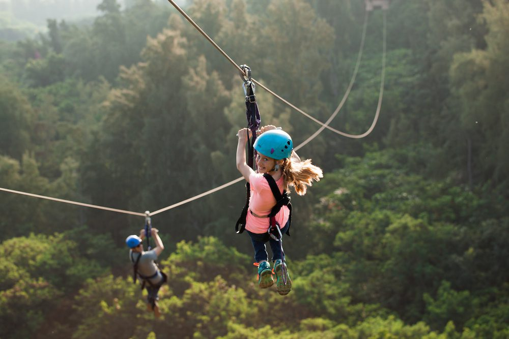 A girl and her father ziplining in Oahu.