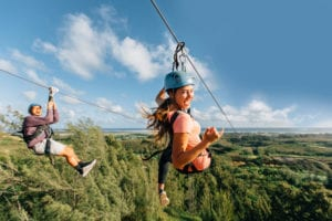 Two guests having fun at our Oahu zipline course.