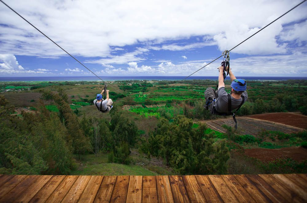 Two guys ziplining in Oahu at CLIMB Works Keana Farms.
