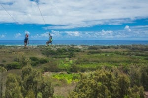 Two people ziplining in Oahu at CLIMB Works Keana Farms.