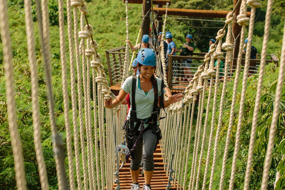 A woman crossing a rope bridge at CLIMB Works Keana Farms.
