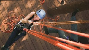 A woman pulling cables during her Oahu zipline adventure.