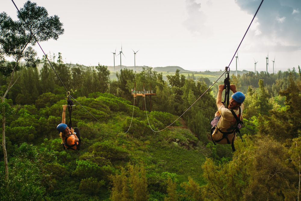 Happy zipliners soaring through the mountains at CLIMB Works Keana Farms.