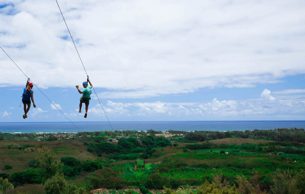 A couple enjoying beautiful views of the ocean while ziplining in Oahu.