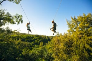 A couple riding one of our ziplines in Oahu.