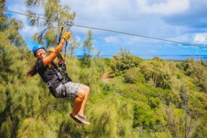 A smiling woman riding one of our Oahu ziplines.