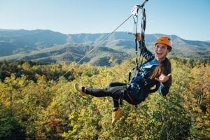 happy girl ziplining in smoky mountains