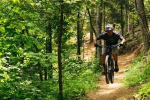 A man mountain biking at CLIMB Works Smoky Mountains.