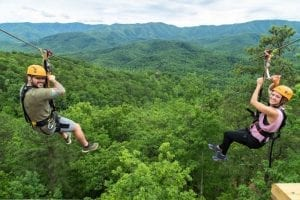 Two friends enjoying the mountaintop ziplines in the Smoky Mountains.