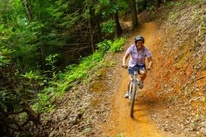 woman mountain biking on trail