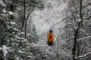 man ziplining in the winter