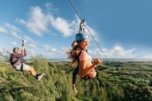friends ziplining in oahu side by side